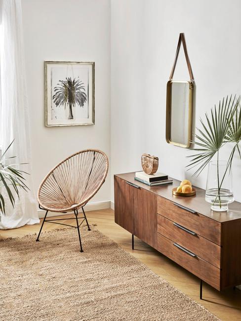 Salon w stylu boho z drewniana komodą, plecionym krzesłem roślinami oraz ozdobami na ścianie