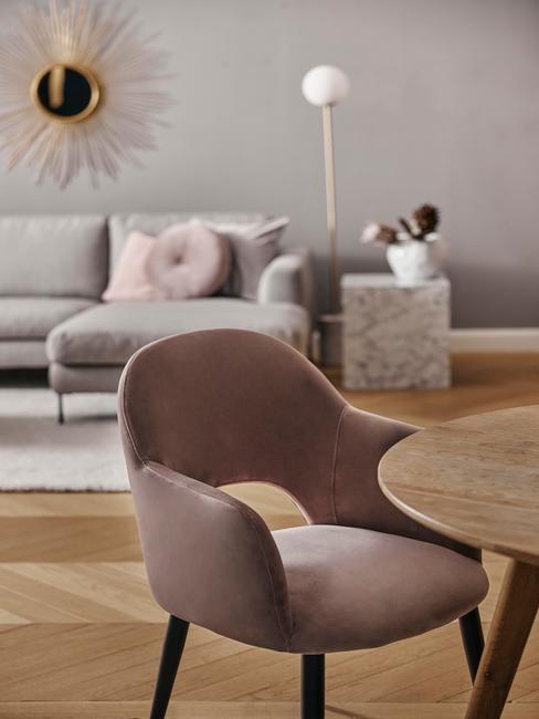 Salon z szraą kanapą, drewnianym stolikiem oraz krzesłem w kolorze budnego różu