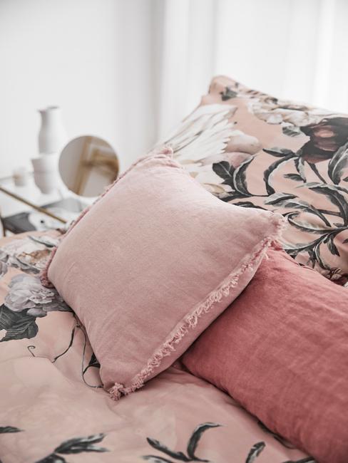 Poduszki w kolorze brudego różu na wzorzystej pościeli