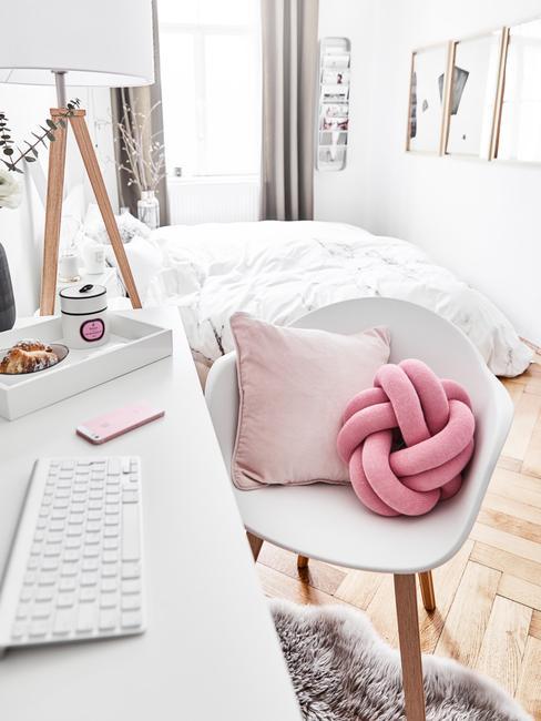 Biała sypialnia z łożkiem, biurkiem oraz krzesłem na której znajduje się różowa poduszka supeł