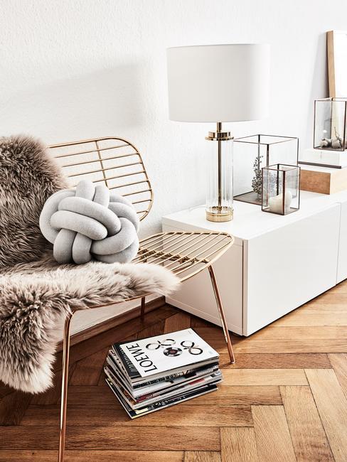 Wnetrze salonu z białą, podłużoną szafką, lampą, fotelem na którym znajduje się poduszka supeł