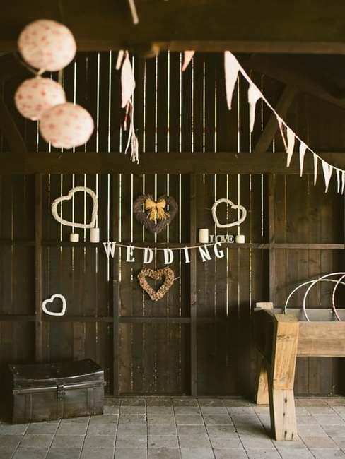 Stoła udekorowana na salę weselną za pomocą białych balonów, chorągiewek oraz girlandy