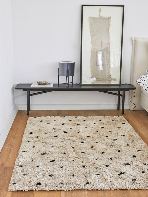 Fragment sypialni z czarną ławką, obrazem oraz białym dywanem w czarne kropki