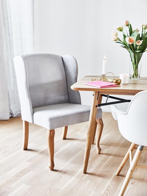 Fragment białego salonu z drewnianym stołem, na któym znajduje się wazon z tulipanami i świeczka