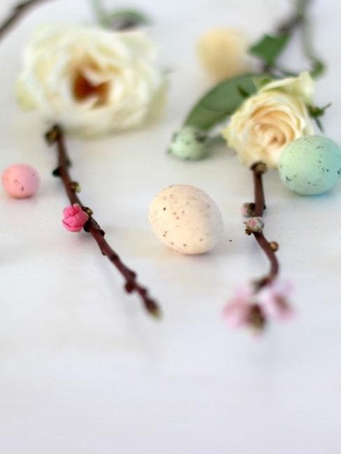 Gałązki, kwiaty róży oraz małe pisanki ułożone na białym stole