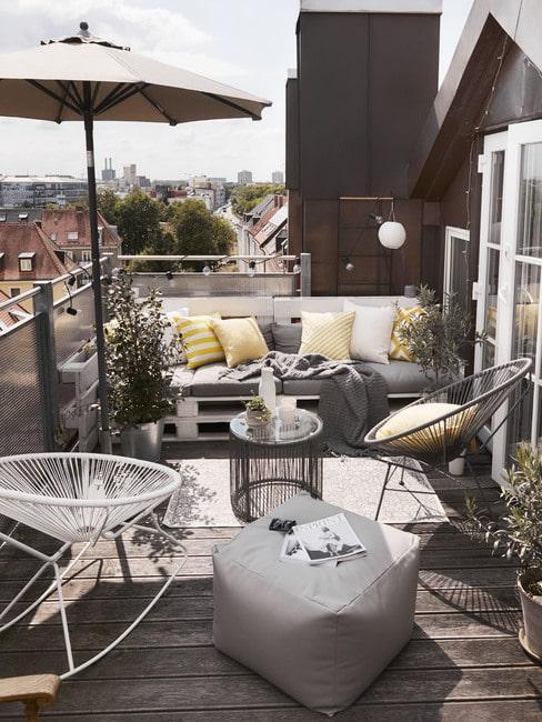 Balkon z drewnianą podłogą i meblami z palet