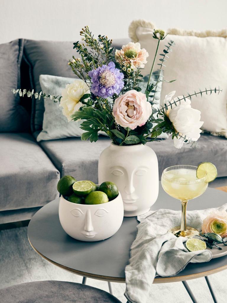 Zbliżenie na wazon z kwiatami, miskę z limonkami oraz kieliszek na szarym stoliku w salonie