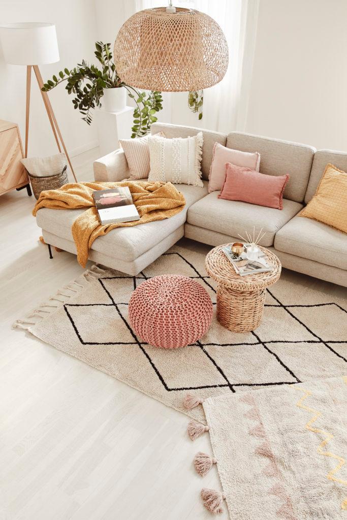 Salon z narożną, beżową sofą, z kolorowymi poduszkami, rattanowym pufem oraz stolikiem