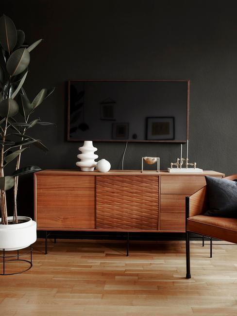 Fragment salonu z ciemną ścianą, rośliną, drewnianą komodą oraz skórzanym fotelem