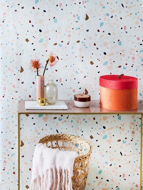 Konsola z przedmiotami dekoracyjnymi przy ścianię z tapetąz motywem terazzo
