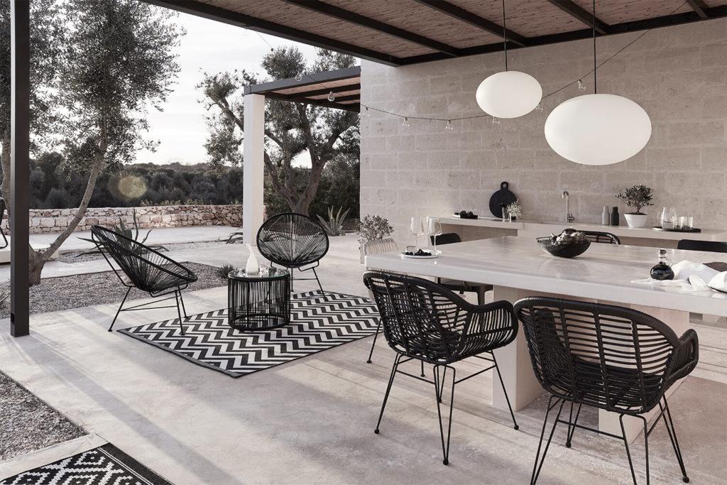 Monochromatyczny taras z czarnymi krzesłąmi, białym stołem i dekoracjami