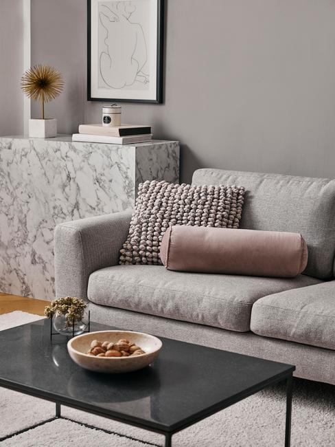 Salonw stylu glam z szarą kanapą, marmurową komodą oraz dekoracjami w kolorze brudnego różu