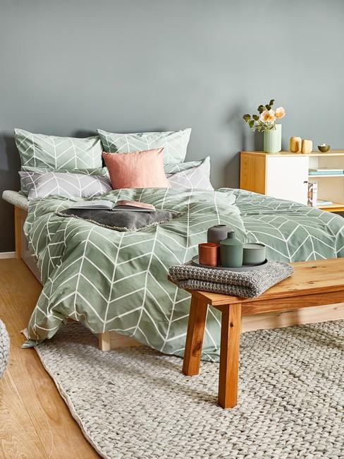 Sypialnia z zielonkawą ścianą oraz drewnianymi meblami