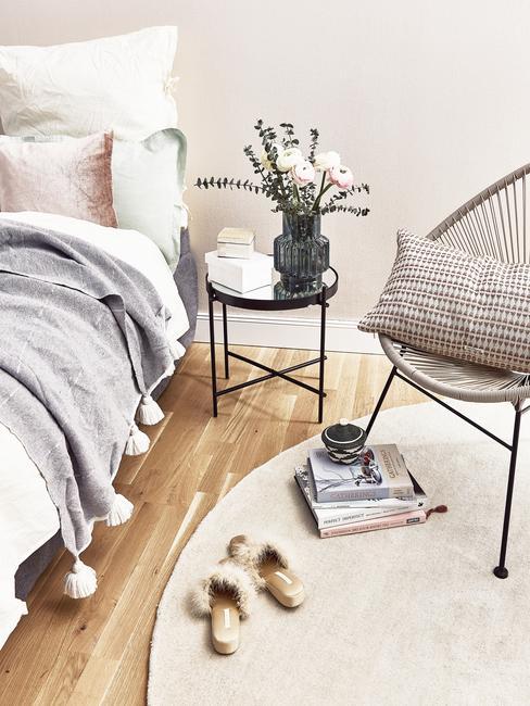 Jasna sypialnia z fotelem, czarnym stolikiem nocnym oraz łóżkiem