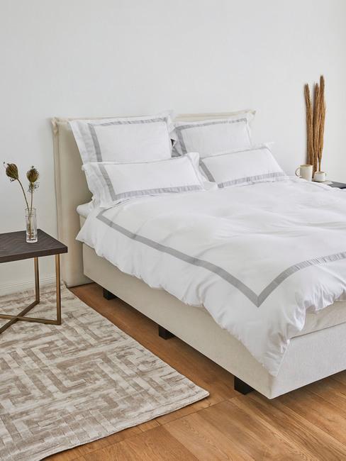 Łóżko z zagłówkiem w jasnej sypialni