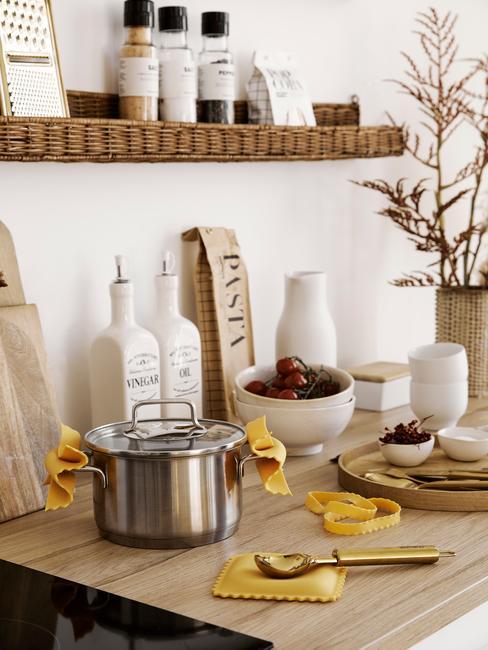 Biała kuchnia z jasnym, drewnianym blatem, półką z rattanu oraz ceramicznymi pojemnikami