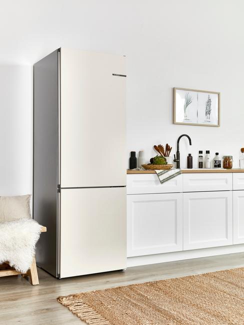 Biały aneks kuchenny w salonie z lodówką, białymi meblami, akcesoriami kuchennymi oraz obrazem na ścianie
