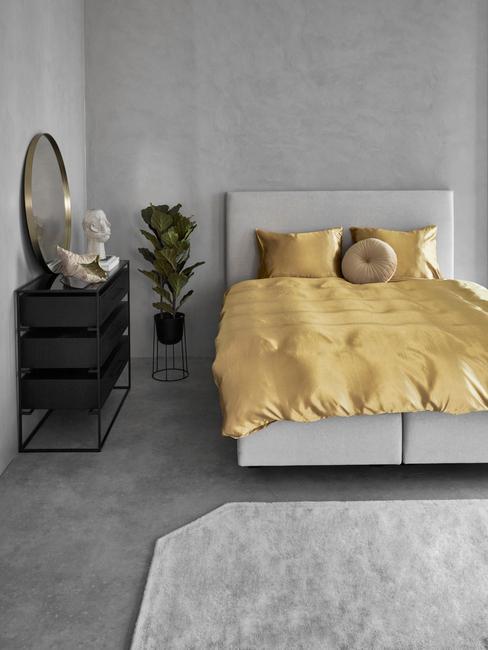 Szara sypialni z łożkiem o żótłej pościeli, dużą rośliną oraz czarną komodą