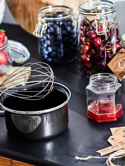 Zbliżenie na czarny garnek oraz szklane słoiki z owocami