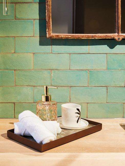 Fragment łazienki z turkusowymi płytkami oraz drewnianą taca z akcesoriami położoną na blacie roboczym