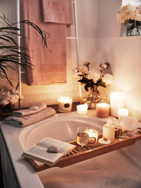 Biała łazienka z wanną oraz dekoracjami w postaci świec oraz tekstyliów