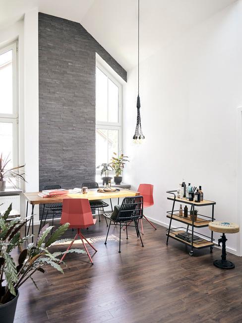 Wysokie pomieszczenie z białymi ścianami i jedną szarą, drewnianymi meblami oraz roślinami