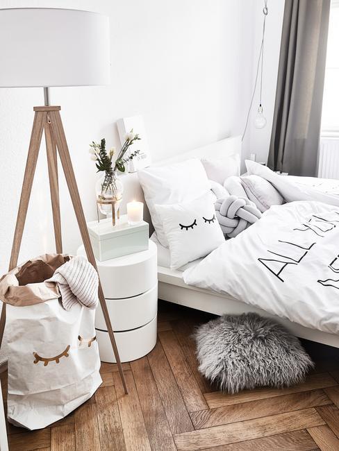 Biała sypialnia z łóżkiem, stolikiem nocnym oraz lampą