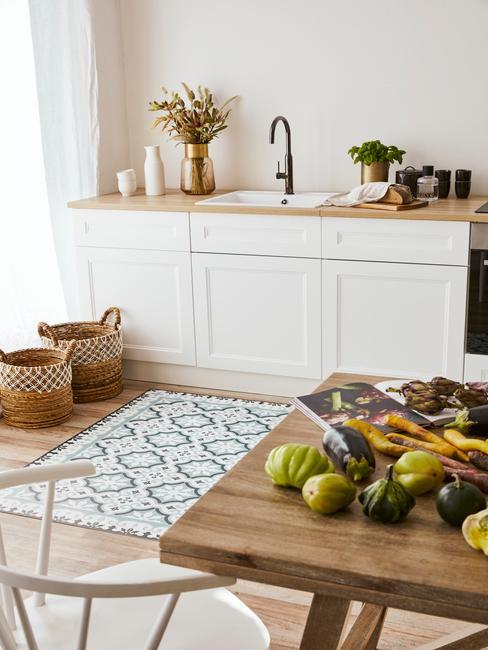 Kuchnia z białymi meblami, koszami rattanowymi, dywanem oraz drewnianym stołem na którym znajdują się owoce