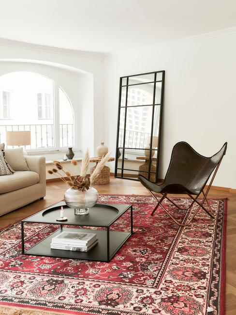 Salon z jasną sofą, dywanem z arabskie wzory, czarnym stolikiem kawowym oraz skórzanym krzesłem