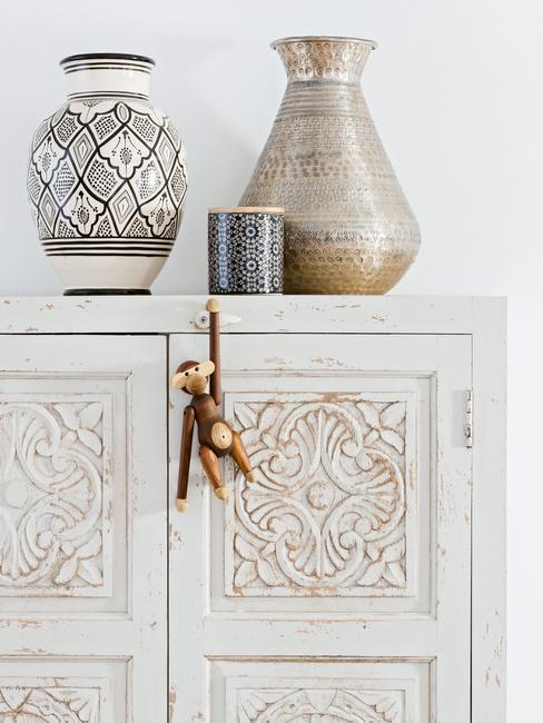 Zbliżenie na białą szafę w style boho z wazonami
