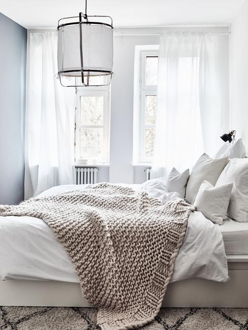 Jasna sypialia z łóżkiem w rozmiarze king size, na którym są ułożone poduszki oraz koc