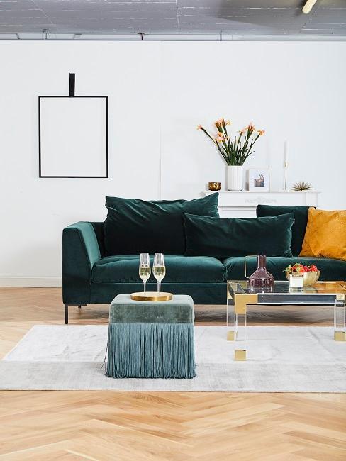 Biały balon z ciemnozioeloną sofą, pufem oraz stolikiem kawowym