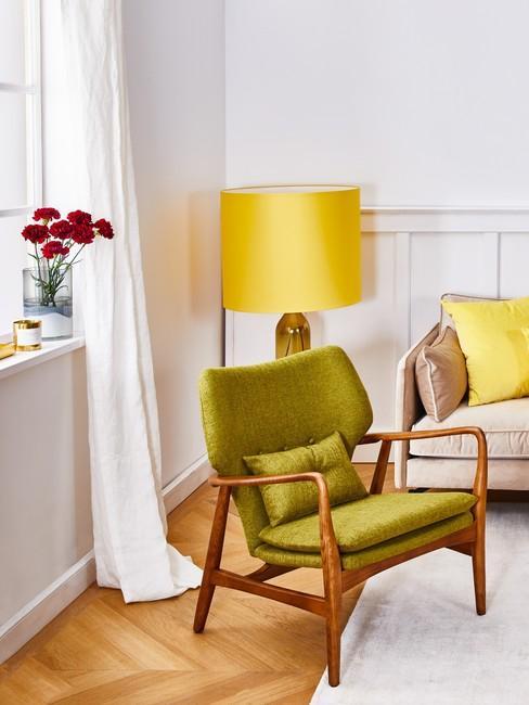 Biały salon z sofą, żółtą lampą oraz pistacjowym fotelem w stylu retro