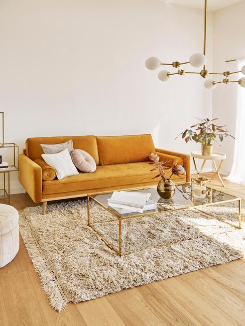 Jasny salon w stylu retro ze szklanym stolikiem kawowym, lampą oraz pomarańczową sofą