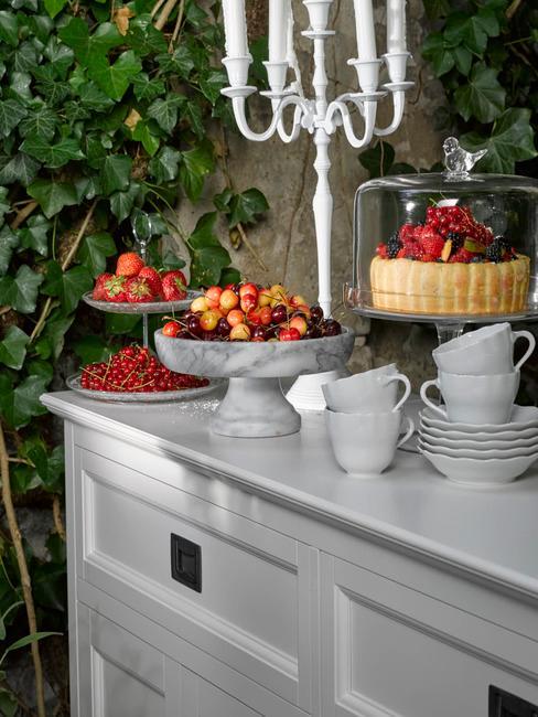Zbliżenie na biały kredens ze świecznikiem, białą zastawą i dekoracjami z owocami