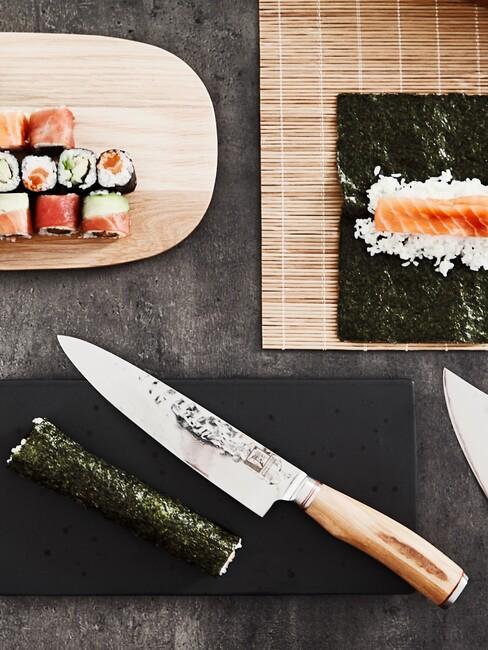 Nóż, mata z rozwiniętą alga, ryżem i łososiem na czarnym stole