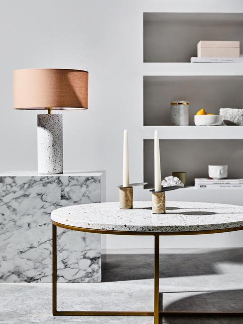 Białe pomieszczenie z półką, marmurowym stolikiem z lampą oraz sotlikiem z lastriko
