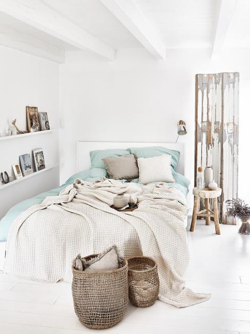 Biała sypialnia w dwuosobowym łożkiem, półkami i dekoracjami w lofcie
