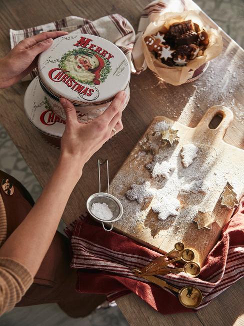 Drewniana deska do krojenia z pierniczkai oraz dekoracyjne pudełko ze świątecznym motywem
