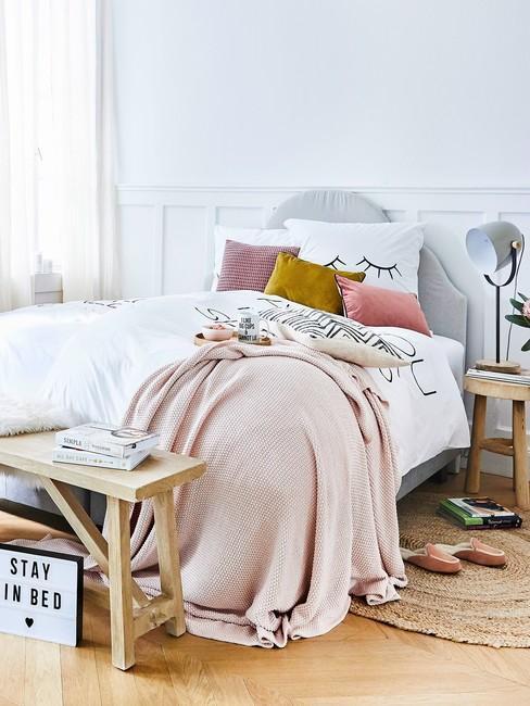 Zbliżenie na łóżko w baiłej sypialni, z drewnianą ławką oraz stolikami nocnymi