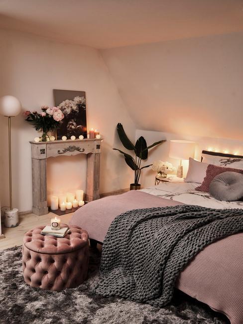 Biała sypialnia w stylu glamour z białą ścianą, dużym łóżkiem, różowym pufem oraz świeczkami