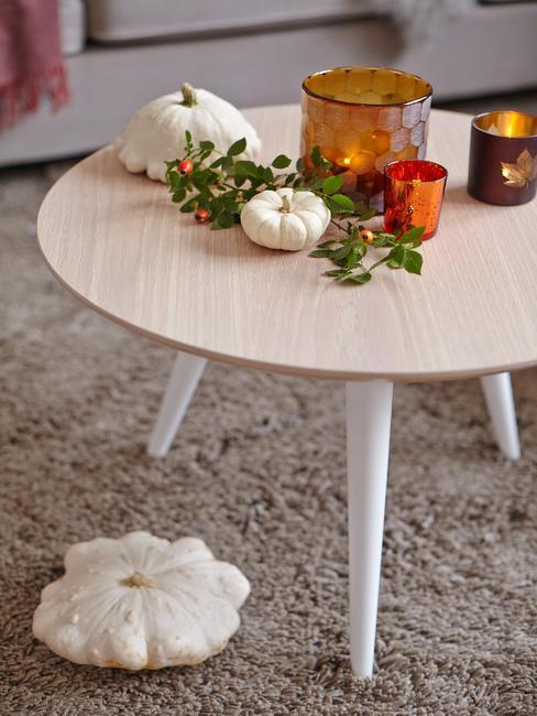 Drewniany stolik na beżowym dywanie z dekoracjami z dyni i świeczkami