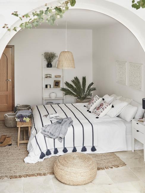 Biała sypialnia z łożkiem, jutowym dywanem, rośliną oraz półką