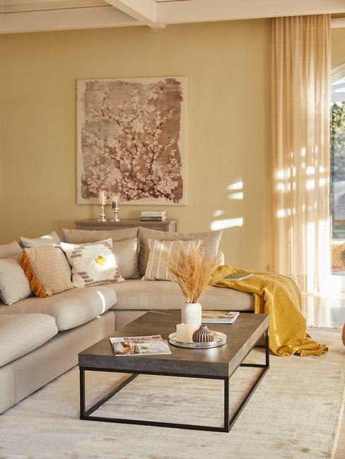 Wnętrze salonu z beżową sofą i drewnianym stolikiem kawowym