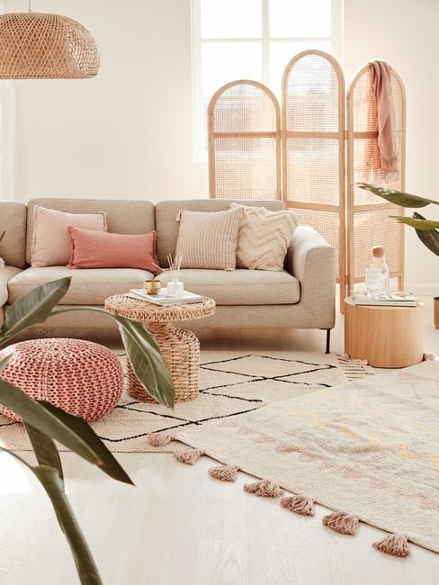 Beżowy salon z sofą, pufem, małym stolikem, rośliną oraz parawanem