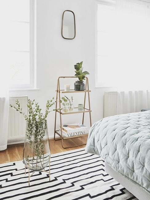 Biała sypialnia z wazonem kwiatów, dywanem w paski, łóżkiem oraz metalową półką
