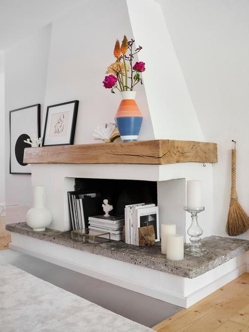 Biały salon z kominkiem, szarym dywanem, obrazami na ścianie