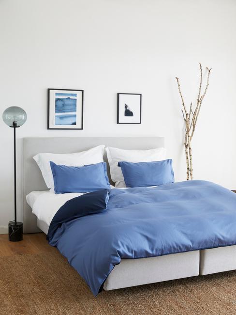 sypialnia w łożkiem, lampą oraz dekoracją z gałęzi
