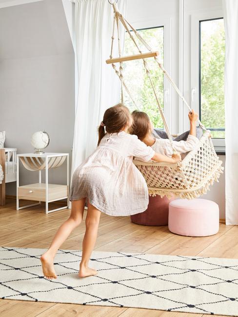 Dwie dziewczynki bawiące się na huśtawce we wnętrzu