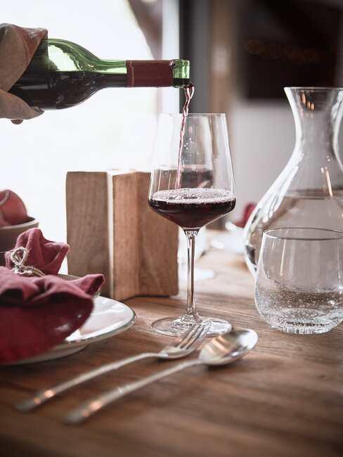 Kieliszek do czerwonego wina położony na drewnianym stole